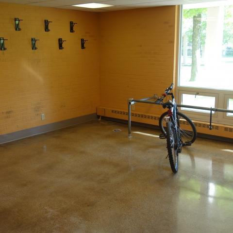 Taft House indoor bike storage space with wall-mounted hooks and ground rack