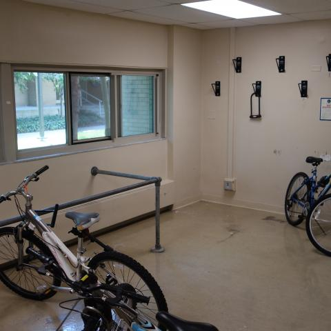 Cutler House Bike Storage Room with wall-mounted hooks, bike rack, and three bikes