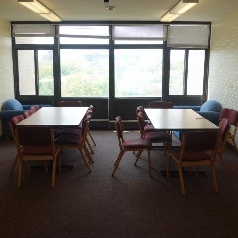 Clarke Tower Upper Floor Lounge with six-foot tables, chairs, and whiteboards