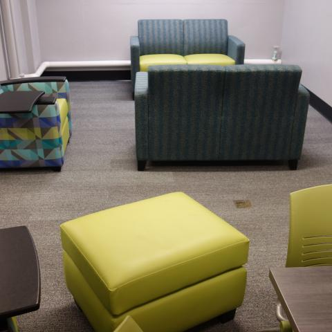 Glaser House Basement Group Study Lounge showing chairs with attached desks, tables, and foot stools