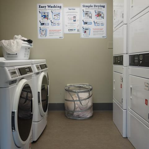 Alumni House 1st Floor Laundry Room with washers, stacked dryers, and two baskets of laundry