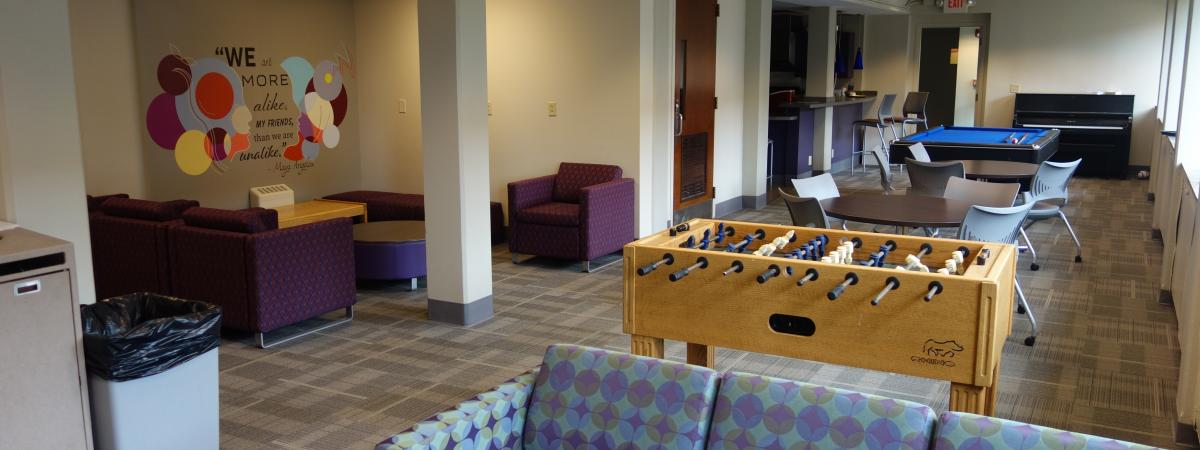 Alumni House common room with furniture, game tables, and mural