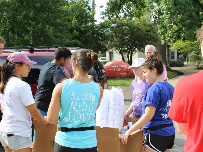 Greek Life Students assisting a freshman family move their belongings to a building