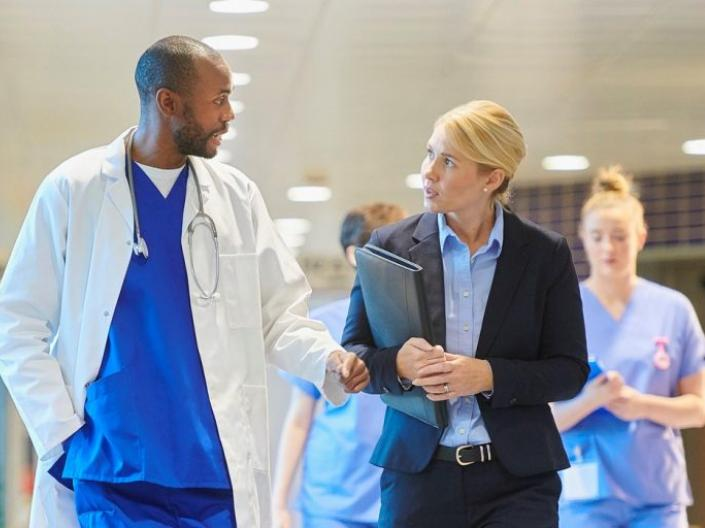 Doctor and business woman walking through hospital hallway